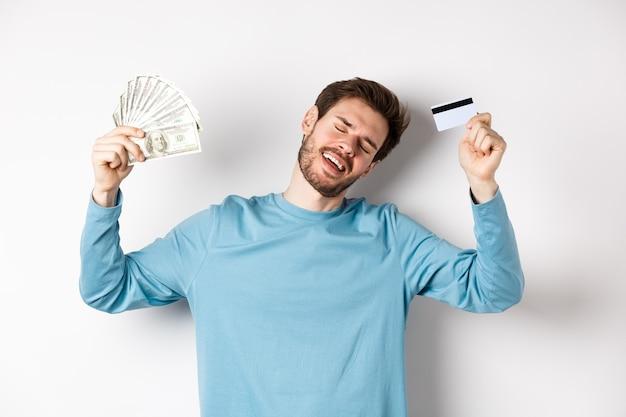 Hombre guapo bailando con dinero y tarjeta de crédito de plástico, de pie en ropa casual sobre fondo blanco.