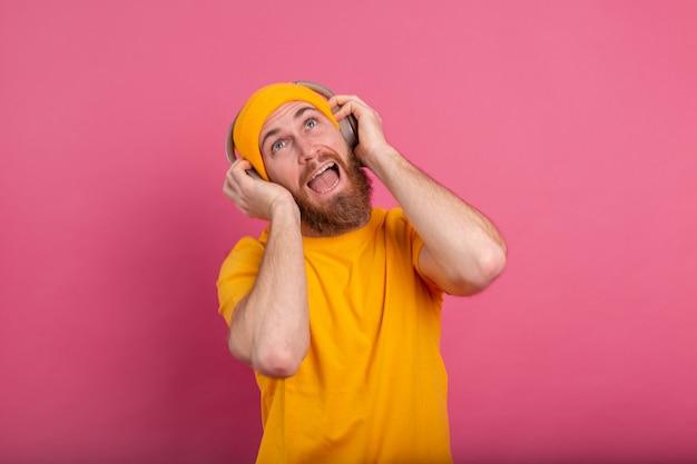 Hombre guapo en baile casual con auriculares aislados sobre fondo rosa