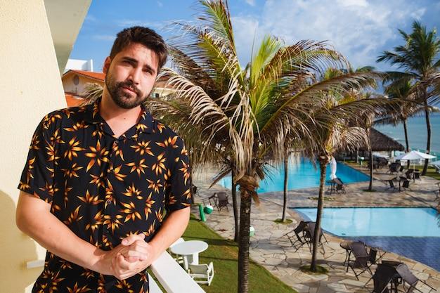 Hombre guapo en el balcón del hotel