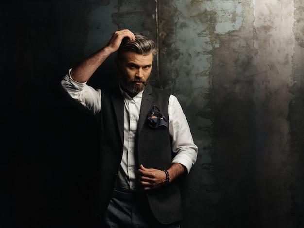 Hombre guapo con barba ajustando su cabello gris y mirando a cámara sobre fondo negro.