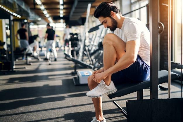 Hombre guapo con barba se ata los cordones de las zapatillas de deporte en el gimnasio antes de los ejercicios.