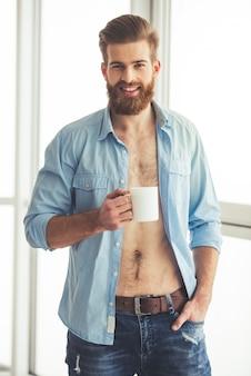 Hombre guapo con barba en camisa desabrochada está sosteniendo una taza