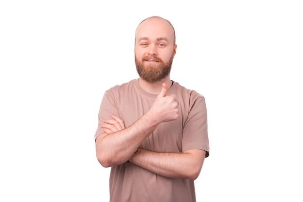 Hombre guapo con barba en camiseta mostrando el pulgar hacia arriba en blanco
