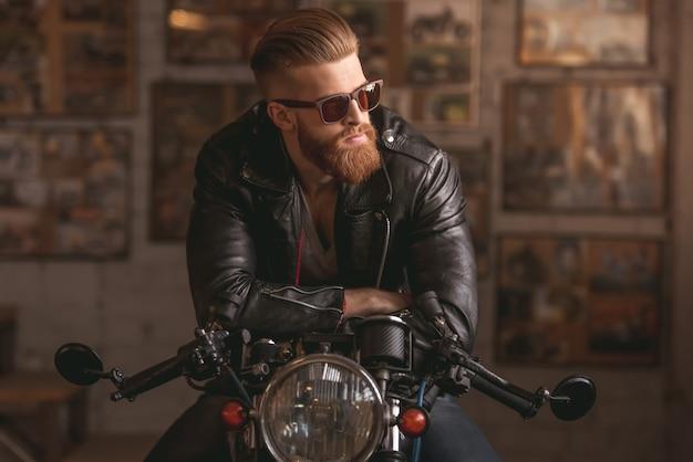 Hombre guapo con barba en chaqueta de cuero y gafas de sol.
