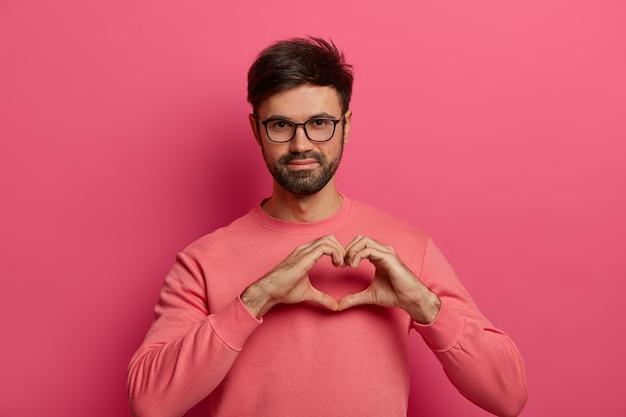 Hombre guapo con barba comparte amor con personas cercanas, forma geart gesto