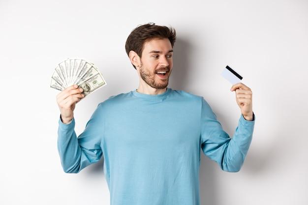 Hombre guapo con barba eligiendo entre dinero y tarjeta de crédito de plástico, pago en efectivo o sin contacto, de pie sobre fondo blanco.