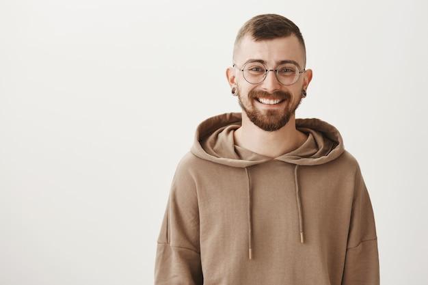 Hombre guapo con barba en gafas sonriendo feliz