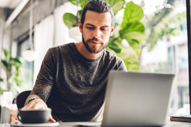 Hombre guapo con barba hipster usa y mira la computadora portátil con café en la mesa en la cafetería concepto de comunicación y tecnología.