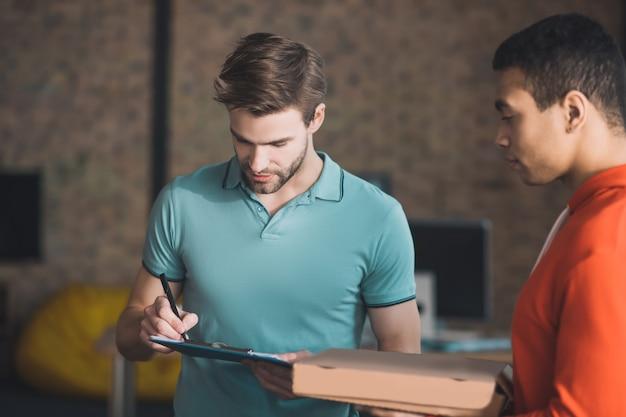 Hombre guapo con barba mirando la factura mientras comprueba dónde firmarla