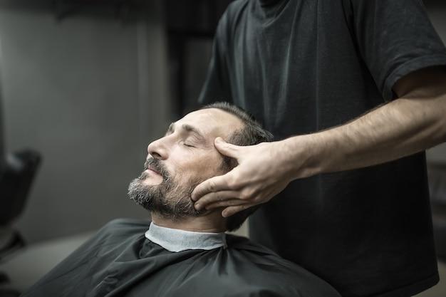 Hombre guapo con barba y ojos cerrados en una capa de pelo de corte negro en la barbería