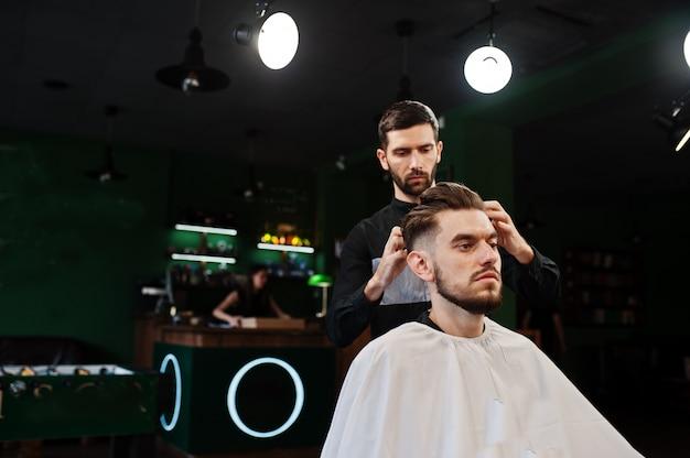 Hombre guapo con barba en la peluquería, barbero en el trabajo.