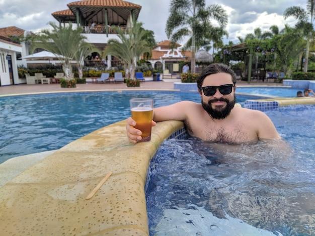 Hombre guapo con barba en una piscina sosteniendo un vaso de cerveza