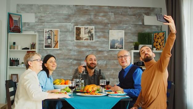 Hombre guapo con barba que usa su teléfono inteligente para tomar un selfie con su familia en la cena.