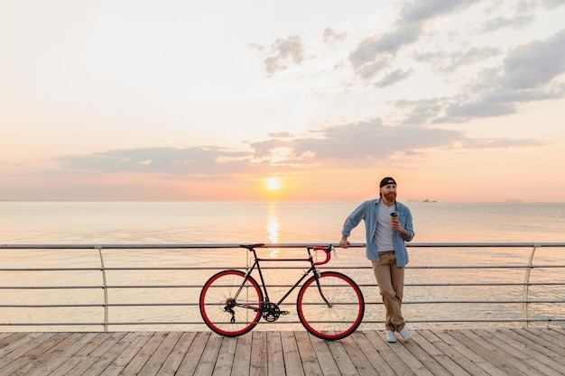 Hombre guapo con barba que viaja con bicicleta en el amanecer de la mañana junto al mar tomando café, viajero de estilo de vida activo y saludable