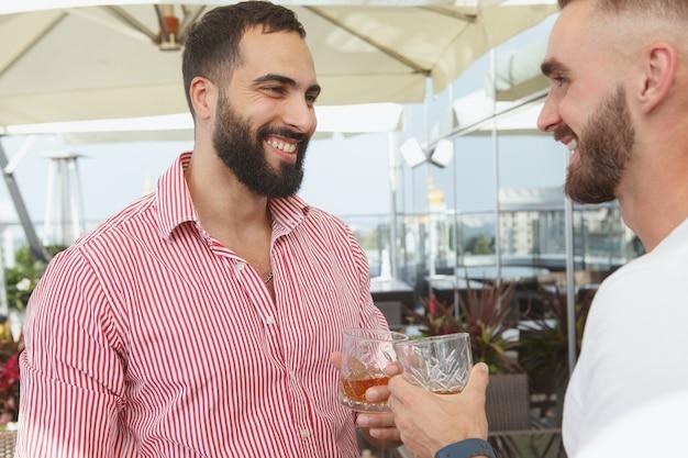 Hombre guapo con barba riendo, disfrutando de bebidas con sus amigos en una fiesta de verano