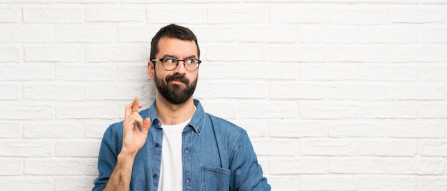 Hombre guapo con barba sobre pared de ladrillo blanco con los dedos cruzados y deseando lo mejor