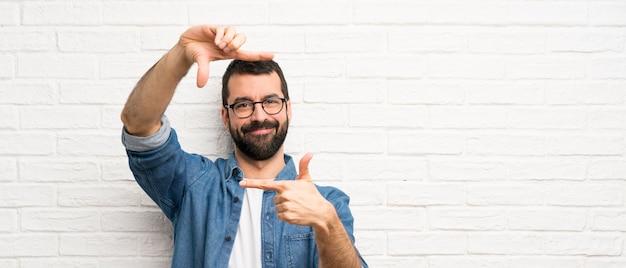Hombre guapo con barba sobre la pared de ladrillo blanco enfocando la cara. símbolo de encuadre