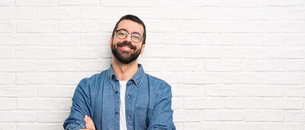 Hombre guapo con barba sobre pared de ladrillo blanco con gafas y feliz