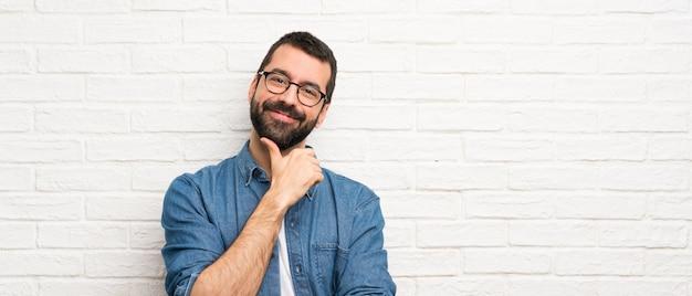 Hombre guapo con barba sobre pared de ladrillo blanco con gafas y sonriendo