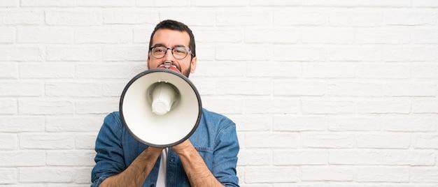 Hombre guapo con barba sobre pared de ladrillo blanco gritando a través de un megáfono