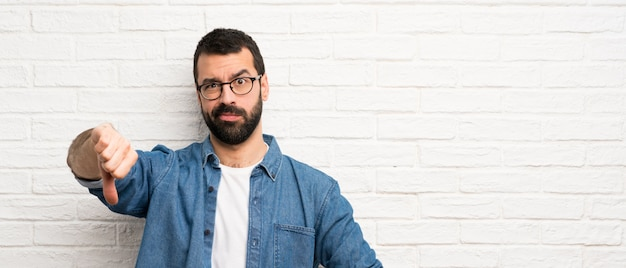 Hombre guapo con barba sobre pared de ladrillo blanco mostrando el pulgar hacia abajo con expresión negativa