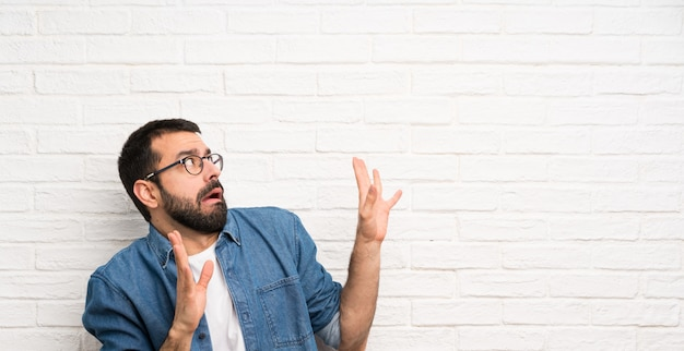 Hombre guapo con barba sobre pared de ladrillo blanco nervioso y asustado