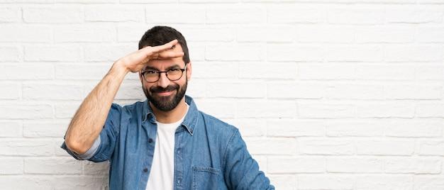 Hombre guapo con barba sobre pared de ladrillo blanco que mira lejos con la mano para mirar algo
