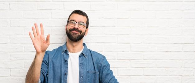 Hombre guapo con barba sobre pared de ladrillo blanco saludando con la mano con expresión feliz