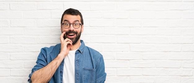 Hombre guapo con barba sobre pared de ladrillo blanco con sorpresa y expresión facial conmocionada