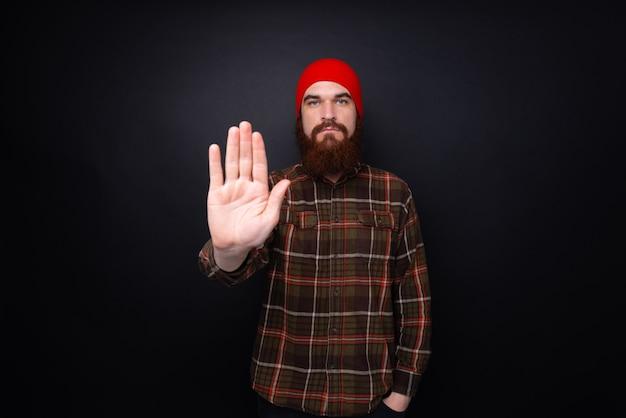 Hombre guapo con barba sobre la pared oscura con la mano abierta haciendo señal de stop con expresión seria y segura, gesto de defensa