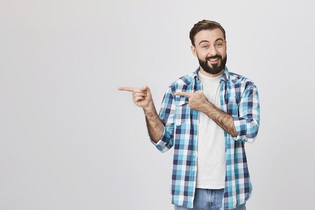 Hombre guapo con barba sonriente apuntando a la izquierda
