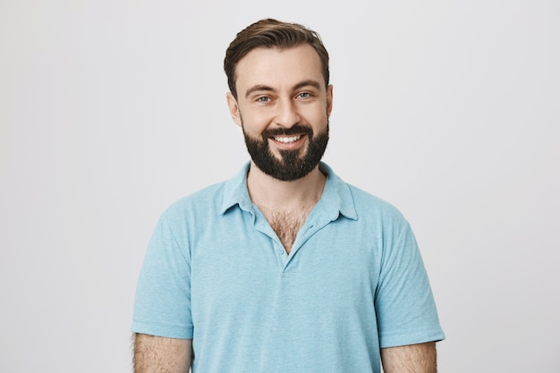 Hombre guapo con barba con sonrisa blanca