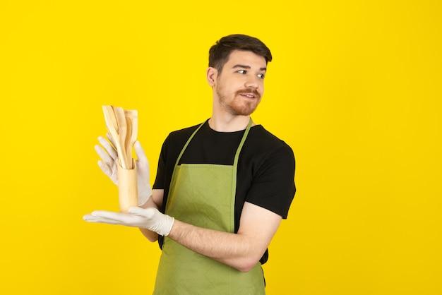 Hombre guapo con barba sosteniendo cucharas de madera y mirando a otro lado en un amarillo.