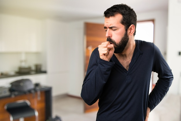 Hombre guapo con barba tosiendo mucho dentro de la casa