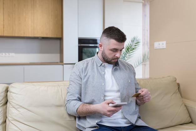 Hombre guapo con barba trabaja en línea desde casa va de compras a una tienda en línea y usa una tarjeta de crédito