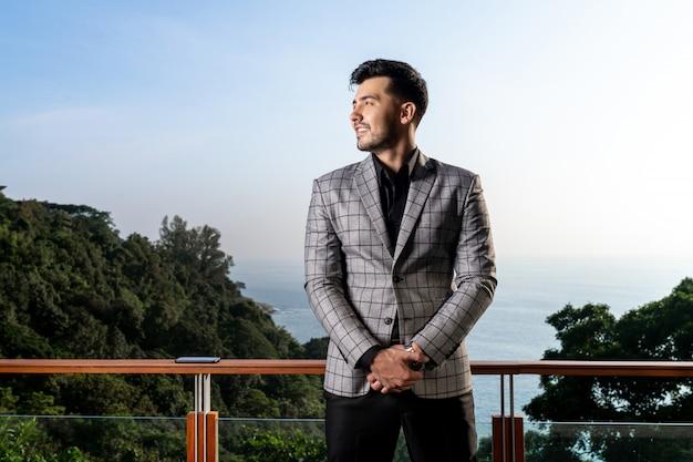 Hombre guapo con barba en un traje formal se encuentra en un balcón con una hermosa vista de la naturaleza
