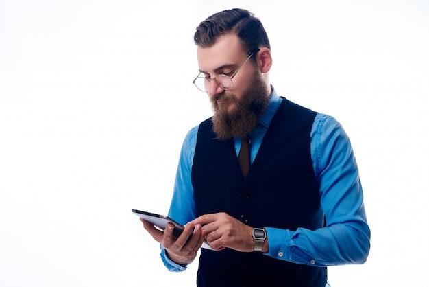 Un hombre guapo con barba, vestido con una camisa azul.