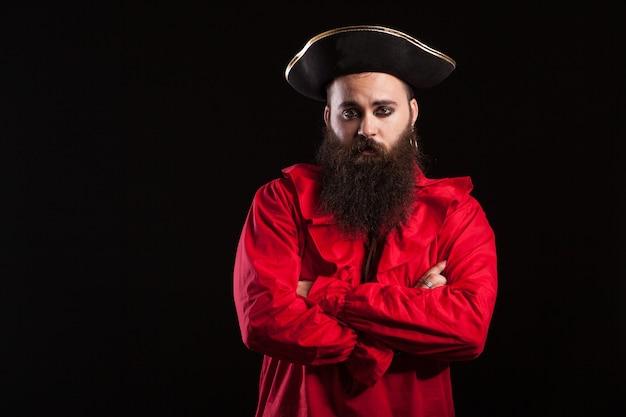 Hombre guapo con barba vestido como un pirata para el carnaval de halloween con los brazos cruzados y mirando a la cámara. hombre de barba larga con traje de marinero.