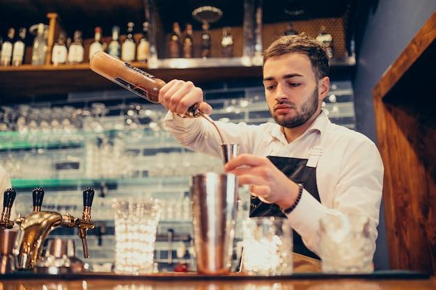 Hombre guapo barman haciendo bebidas y cócteles en un mostrador