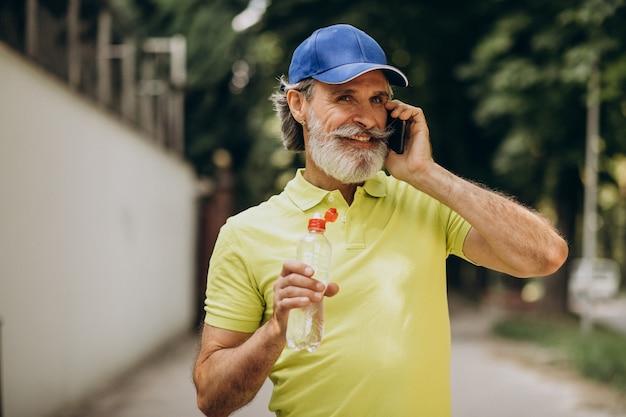 Hombre guapo bebiendo agua en el parque después de trotar