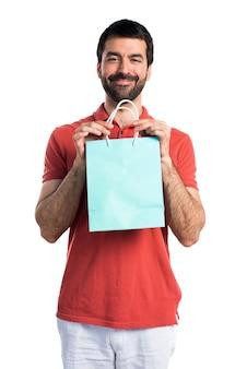 Hombre guapo con la bolsa de compras
