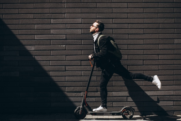 Hombre guapo cabalgando en la ciudad en scooter