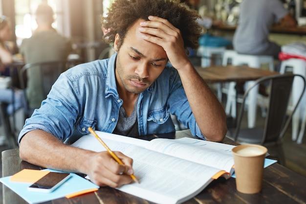 Hombre guapo con cabello oscuro y rizado vestido casualyy sentado en un acogedor café tomando café con la mirada fija en el libro escribiendo las cosas principales sosteniendo la mano en la frente con dolor de cabeza y cansancio