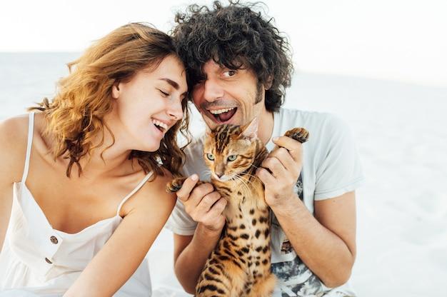 Un hombre guapo de cabello rizado abraza suavemente a su amada. tienen un gato en sus manos. al fondo hay una tela gris.