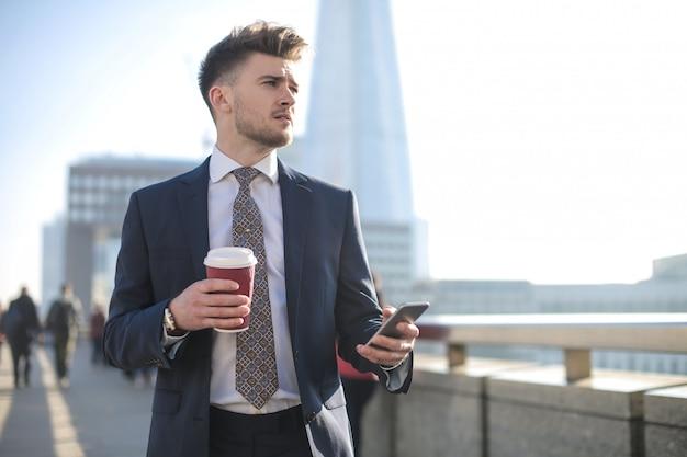 Hombre guapo caminando en la calle, revisando su teléfono y tomando café