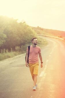 Hombre guapo caminando por un camino rural. filtro de instagram vintage retro