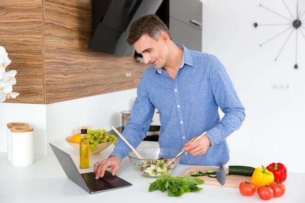 Hombre guapo con camisa azul usando laptop y cocinando en la cocina de casa