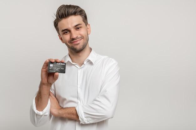Hombre guapo con camisa blanca mostrando su tarjeta de crédito de pie sobre fondo blanco.