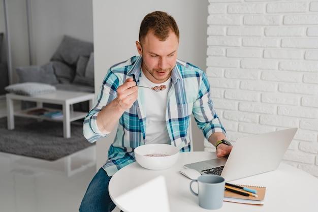 Hombre guapo en camisa desayunando en casa en la mesa trabajando en línea en la computadora portátil desde casa