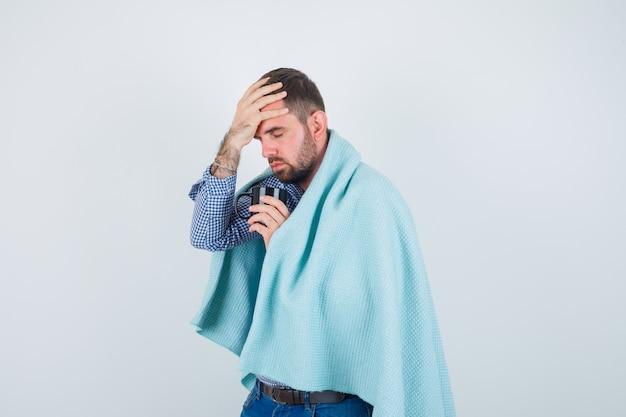 Hombre guapo en camisa, jeans, chal sosteniendo una taza de té, con dolor de cabeza y mirando exhausto, vista frontal.